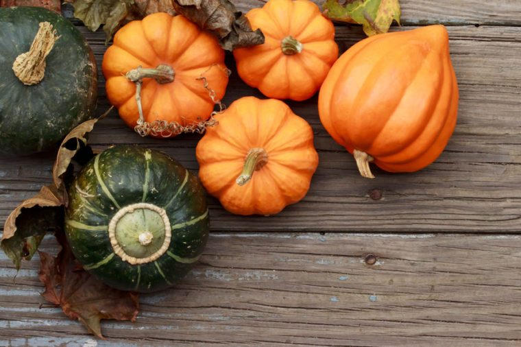 Autumn pumpkins with leaves on wooden board