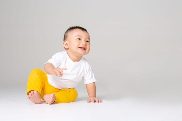funny baby boy sitting on white background