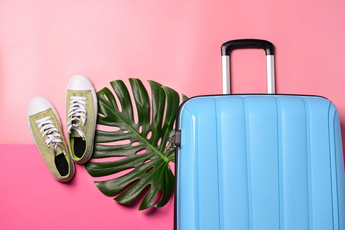 Suitcase, shoes and tropical leaf on color background. Travel concept