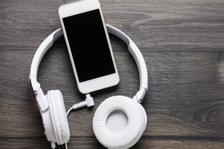 White headphones connected to white smartphone