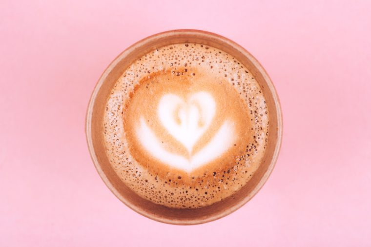 Paper cup of coffee to go on pink trendy pastel background from above, flat lay