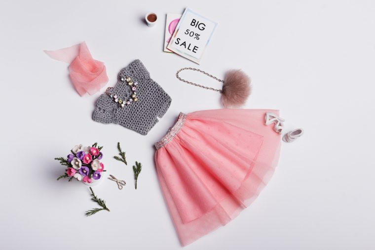 Fashion Concept. Crochet grey blouse and powdery pink tulle skirt with fur handbag, jewelry, shoes, magazines, cup of coffee, bouquet of flowers. Hand-made clothes for 11-inch doll.