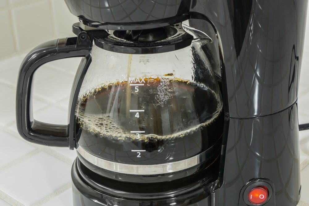 Coffee maker pot filling close up.