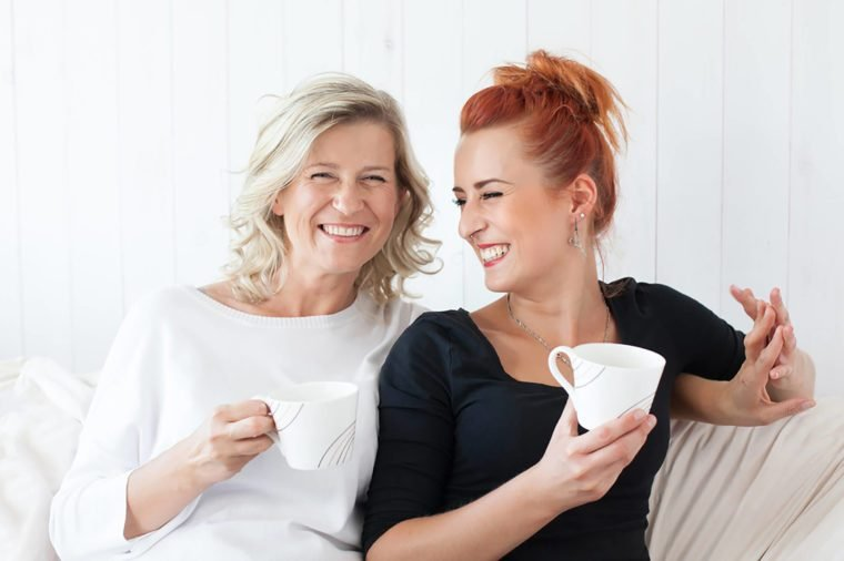 Mother and daughter smiling while drinking coffee