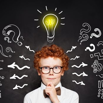 Redhead kid boy with lightbulb on blackboard background. Brainstorming and idea concept