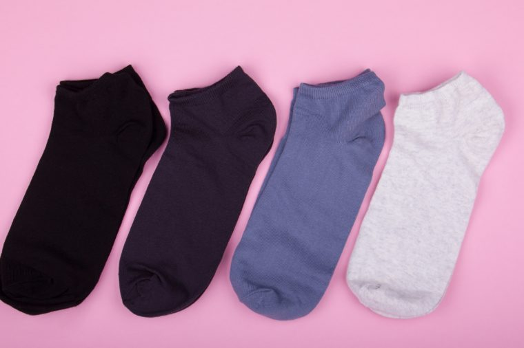 four pairs of different colored socks on a pink background