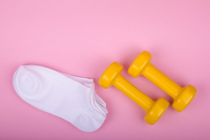 yellow dumbbells and white socks on a pink background