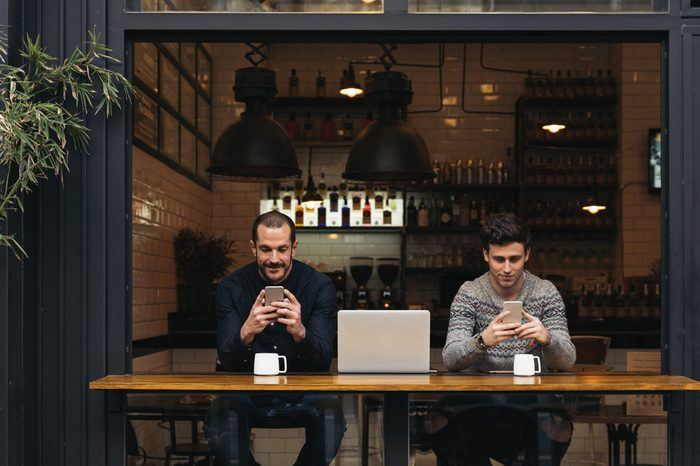 Friends using mobile and laptop in a coffee shop.
