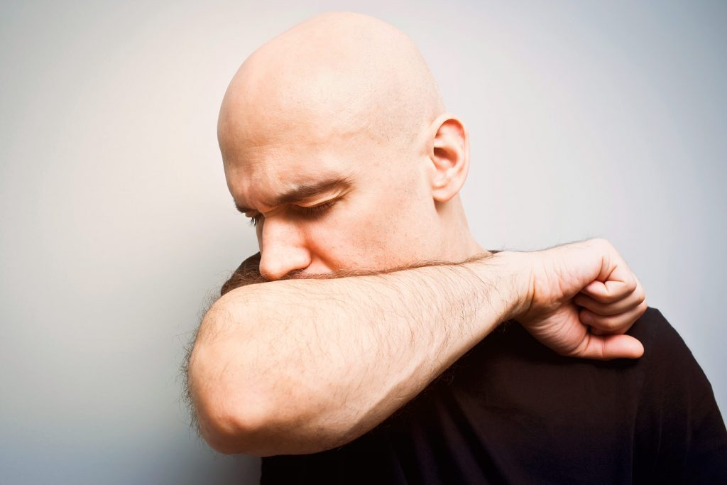 Bald Caucasian man coughing into his arm