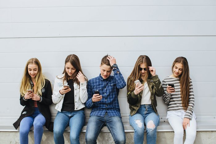 Group of teenagers sitting outdoors using their mobile phones