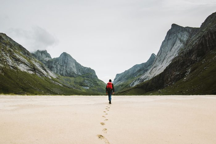Man with backpack walking away alone at sandy beach in mountains Travel lifestyle concept adventure outdoor summer vacations in Norway wild nature