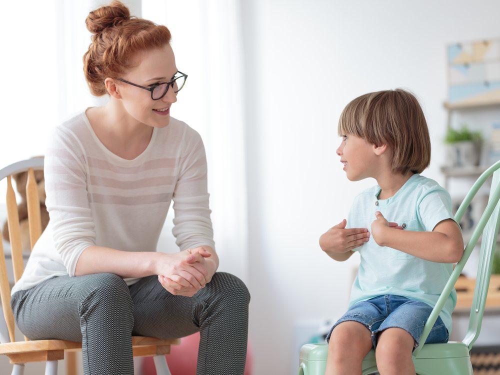 Smiling woman talking to child during therapy session