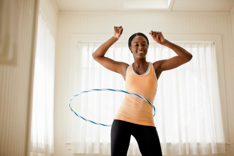 Happy young woman hula hooping in her living room.