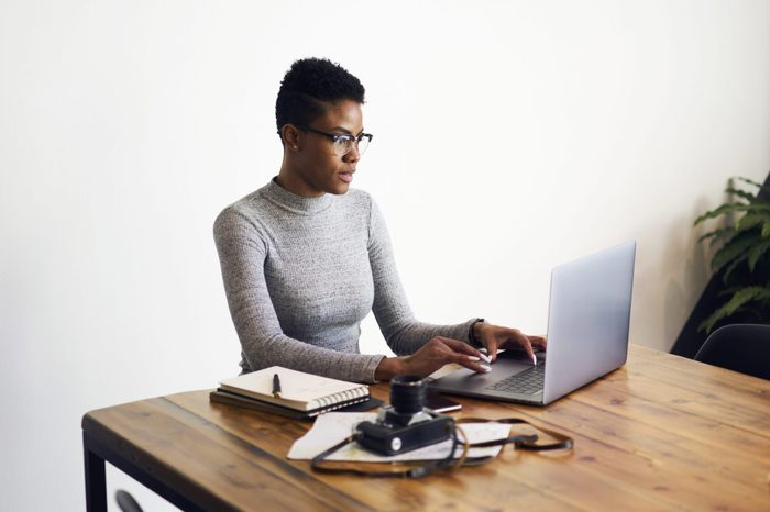 Attractive afro american businesswoman using laptop computer for working online doing distance job in coworking space,professional photographer editing pictures via application on laptop computer