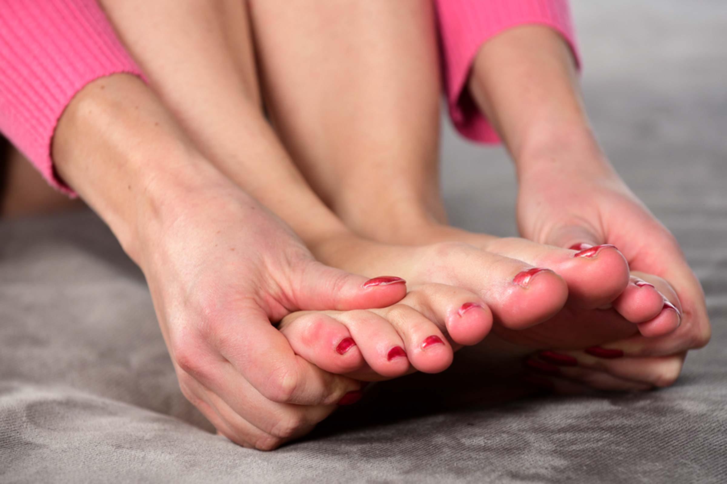 woman rubbing feet