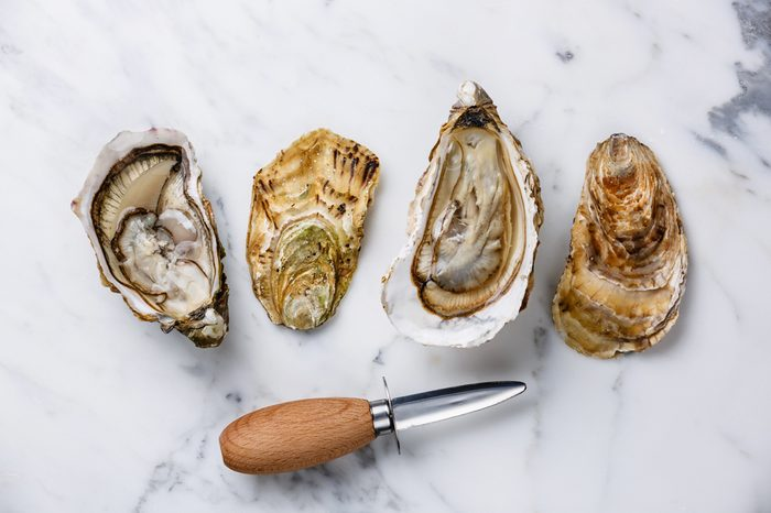 Shucked Oysters Fines de Claire and oyster knife on white marble background