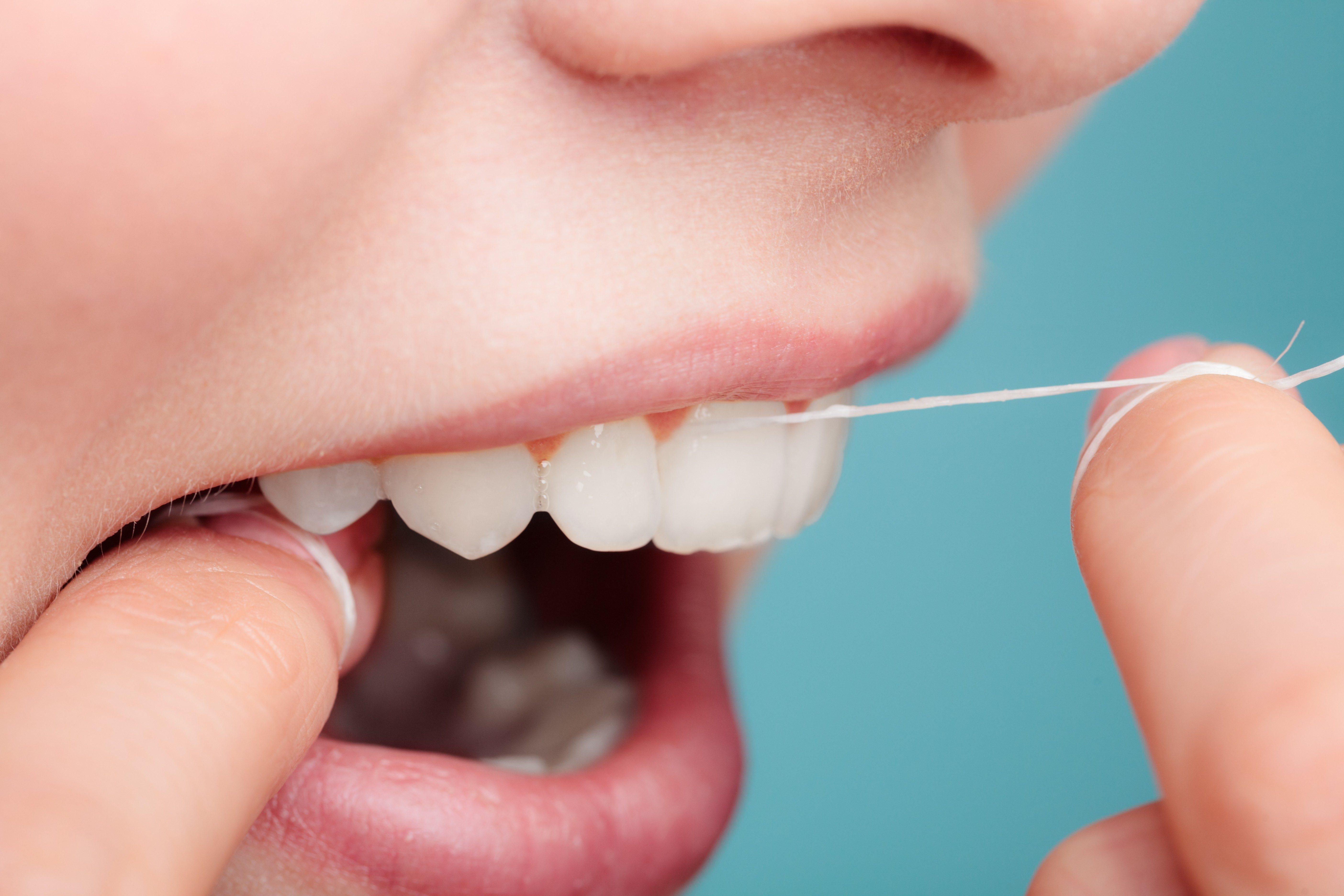 Women flossing her teeth