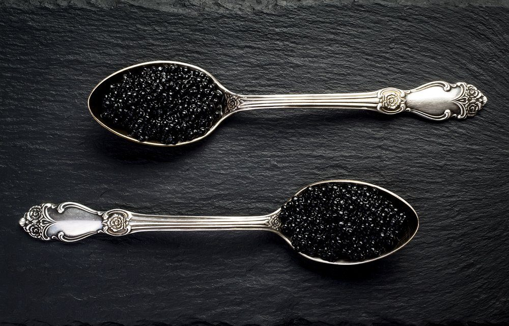 Two vintage silver spoons with black sturgeon caviar on black slate stone background. Top view, flat lay, copy space.
