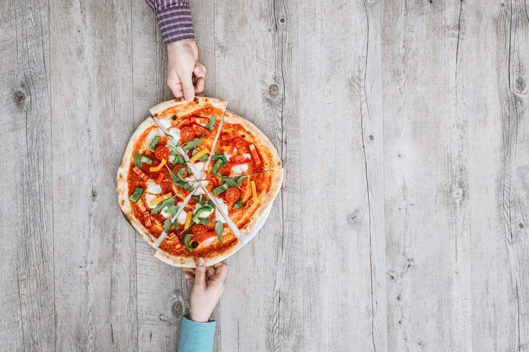 hands grabbing slices of pizza