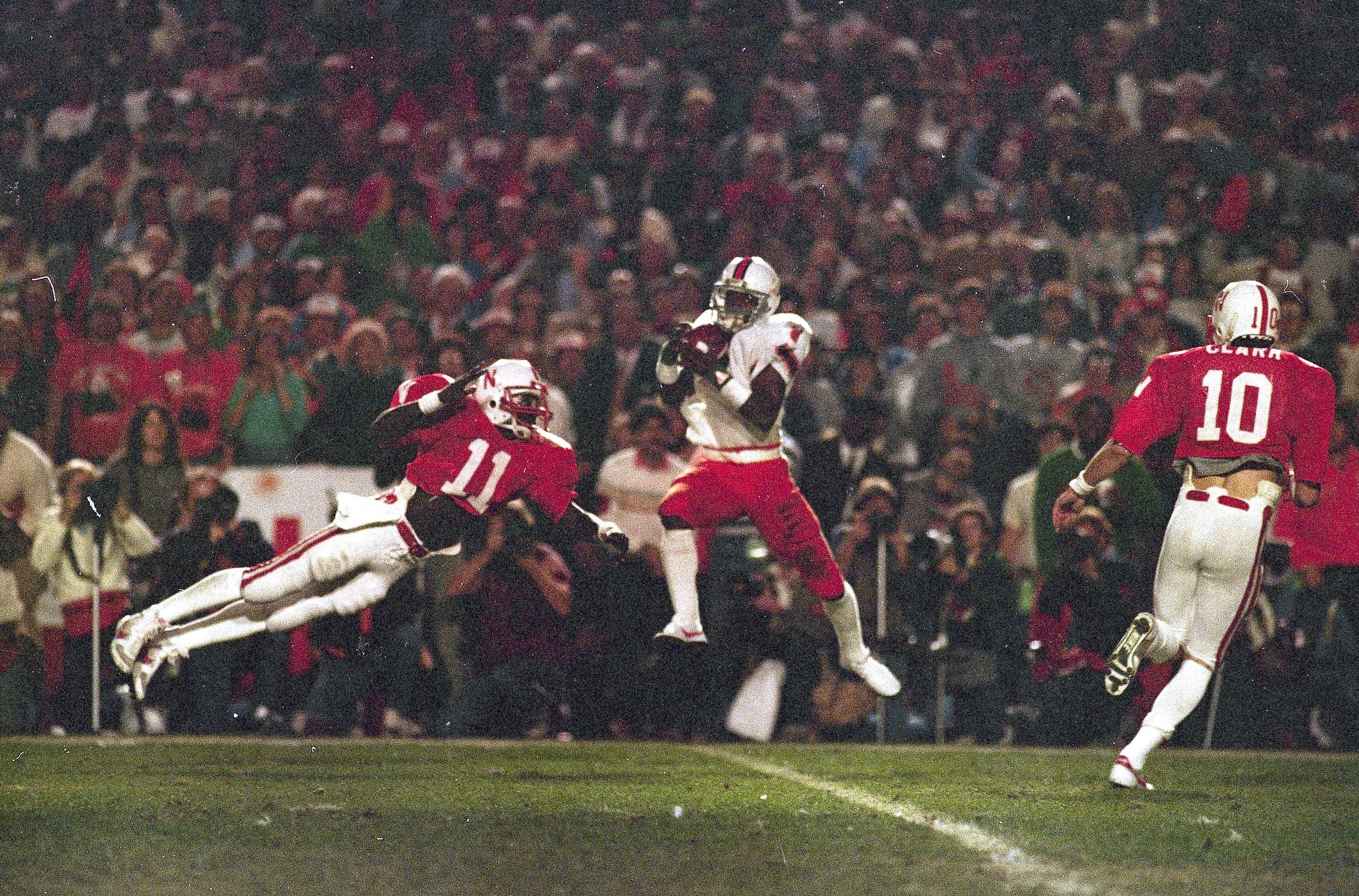 Mandatory Credit: Photo by John Raoux/AP/Shutterstock (6569113a) University of Miami wide receiver Stanley Shakespeare (6) leaps high to gather a first quarter pass from quarterback Bernie Kosar against the University of Nebraska in the Orange Bowl game in Miami, . Flying through the air to defend is Nebraska cornerback Neil Harris (11 Orange Bowl Miami Nebraska 1984, Miami, USA