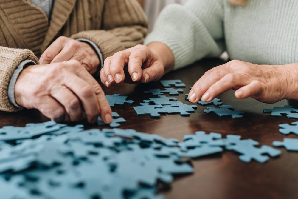 cropped view of retired couple playing with puzzles at home