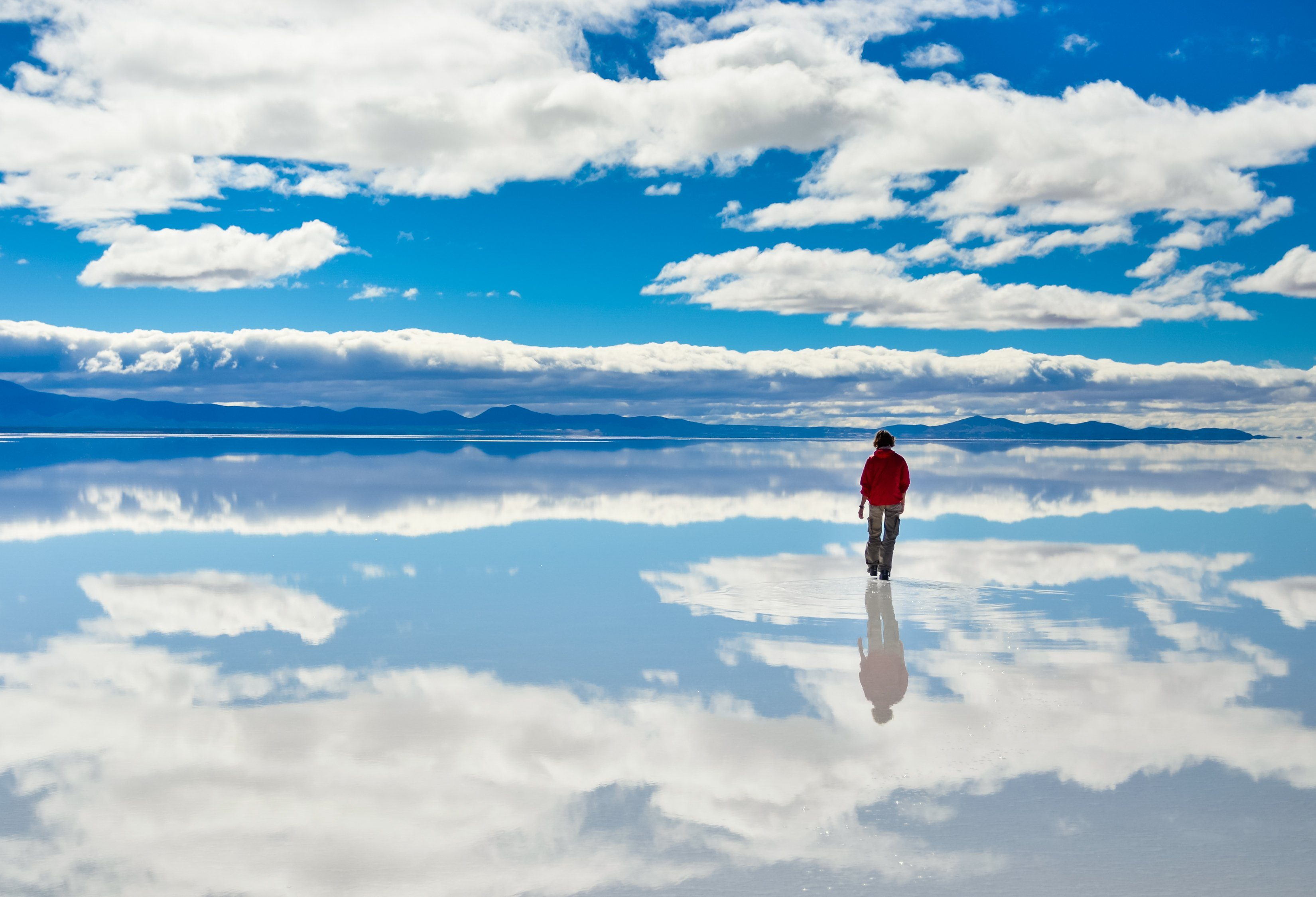 Girl in red on Salar de Uyuni in Bolivia covered with water with cloudy sky reflections