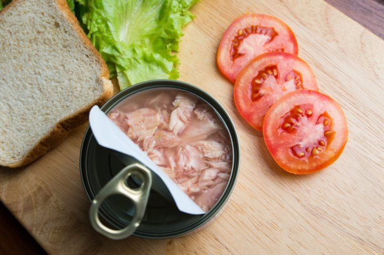 Preparing tuna sandwich, tuna in can opened with bread, lettuce, and tomato on wood background