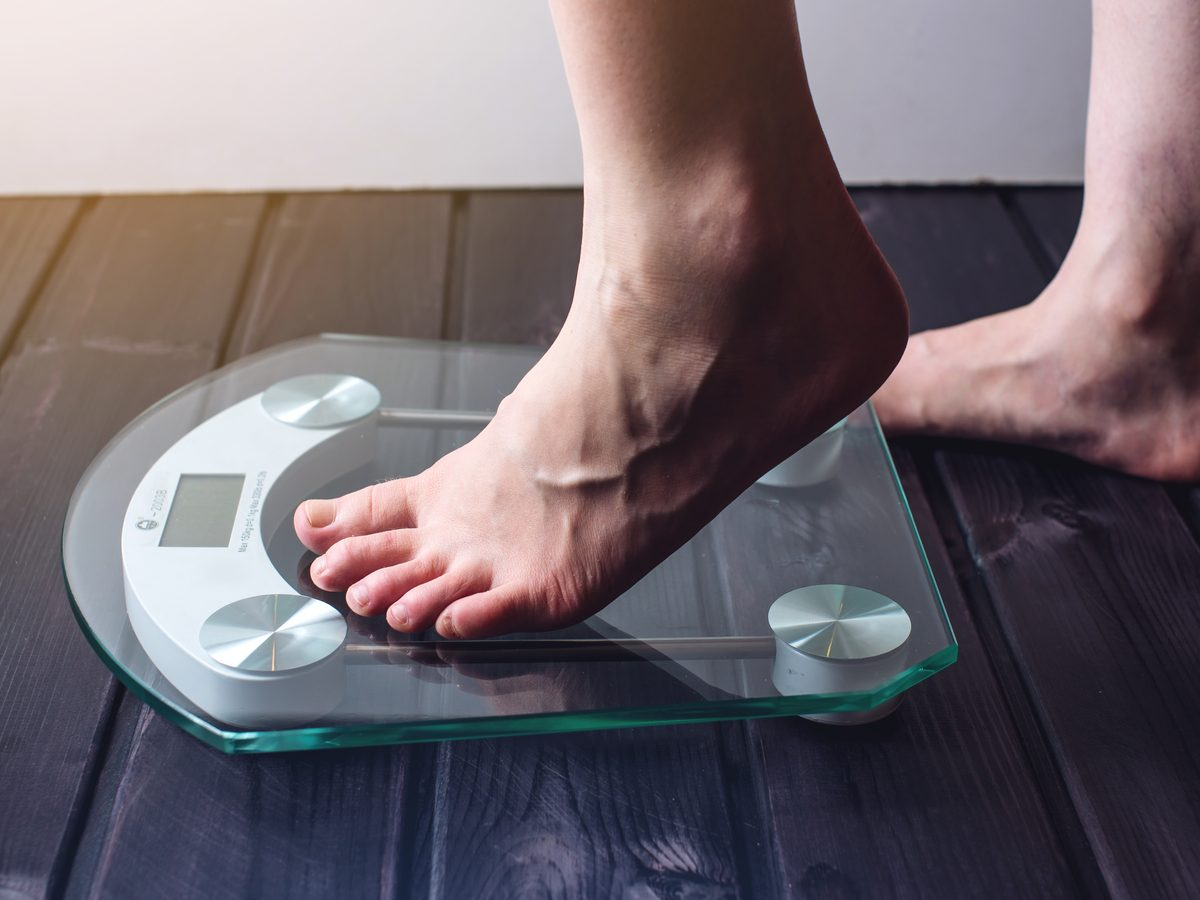 Female feet stepping on weight scale