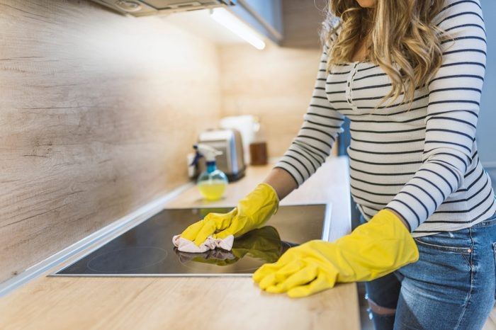 people, housework and housekeeping concept - close up of woman hand in protective glove with rag cleaning oven at home kitchen. Close up of woman cleaning cooker at home kitchen