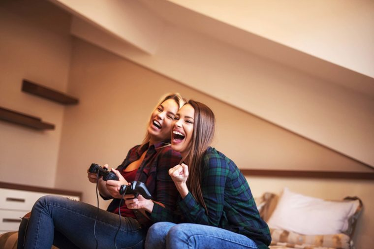 Two female friends playing a game console
