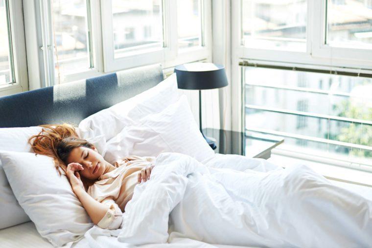 Woman sleeping in bright bedroom