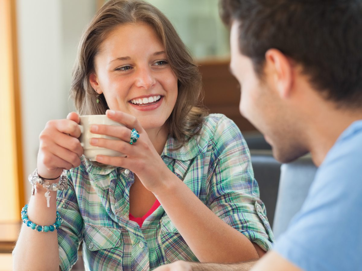 Smiling woman talking to male companion over coffee