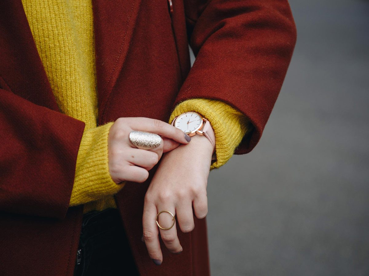 Stylish woman looking at time on wristwatch