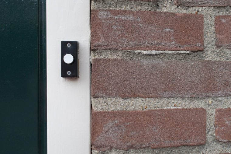 Black and white doorbell at the door of a living house