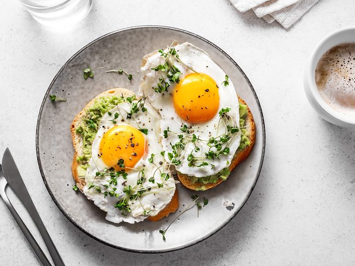 Metabolism boosting foods - Avocado Egg Sandwiches and coffee for healthy breakfast. Whole grain toasts with mashed avocado, fried eggs and organic microgreens on white table.