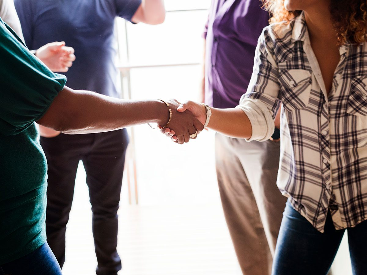 A good party guest being social shaking hands