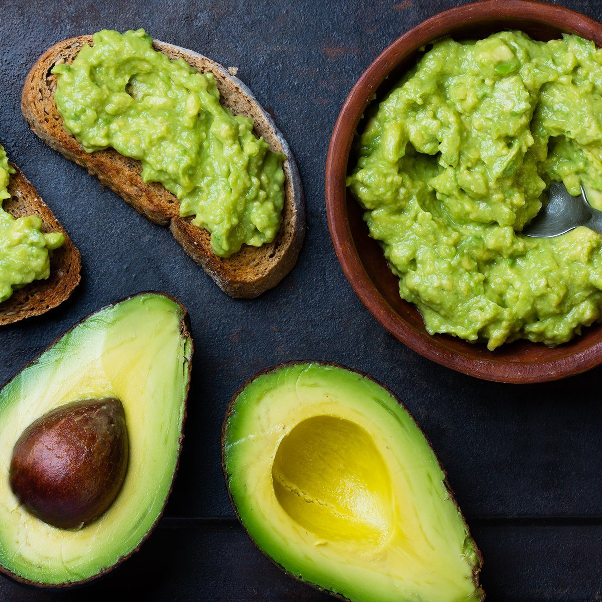 Traditional latinamerican mexican sauce guacamole in clay bowl, cut half avocado and avocado sandwiches on dark background.