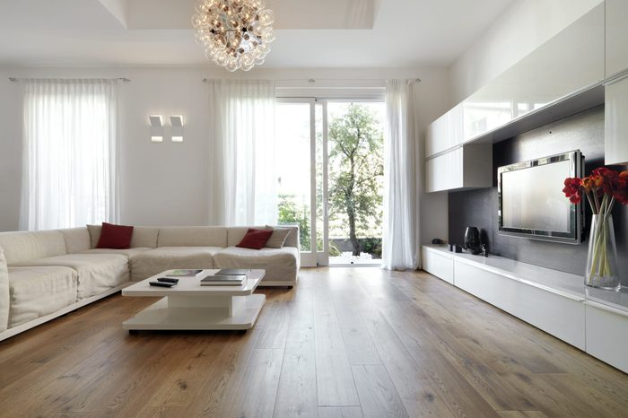 internal view of a modern living room with wood flooring overlooking on the garden