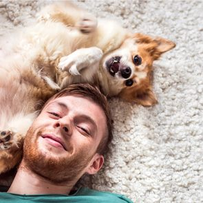 How to be happy - Young smiling man playing with his pet dog