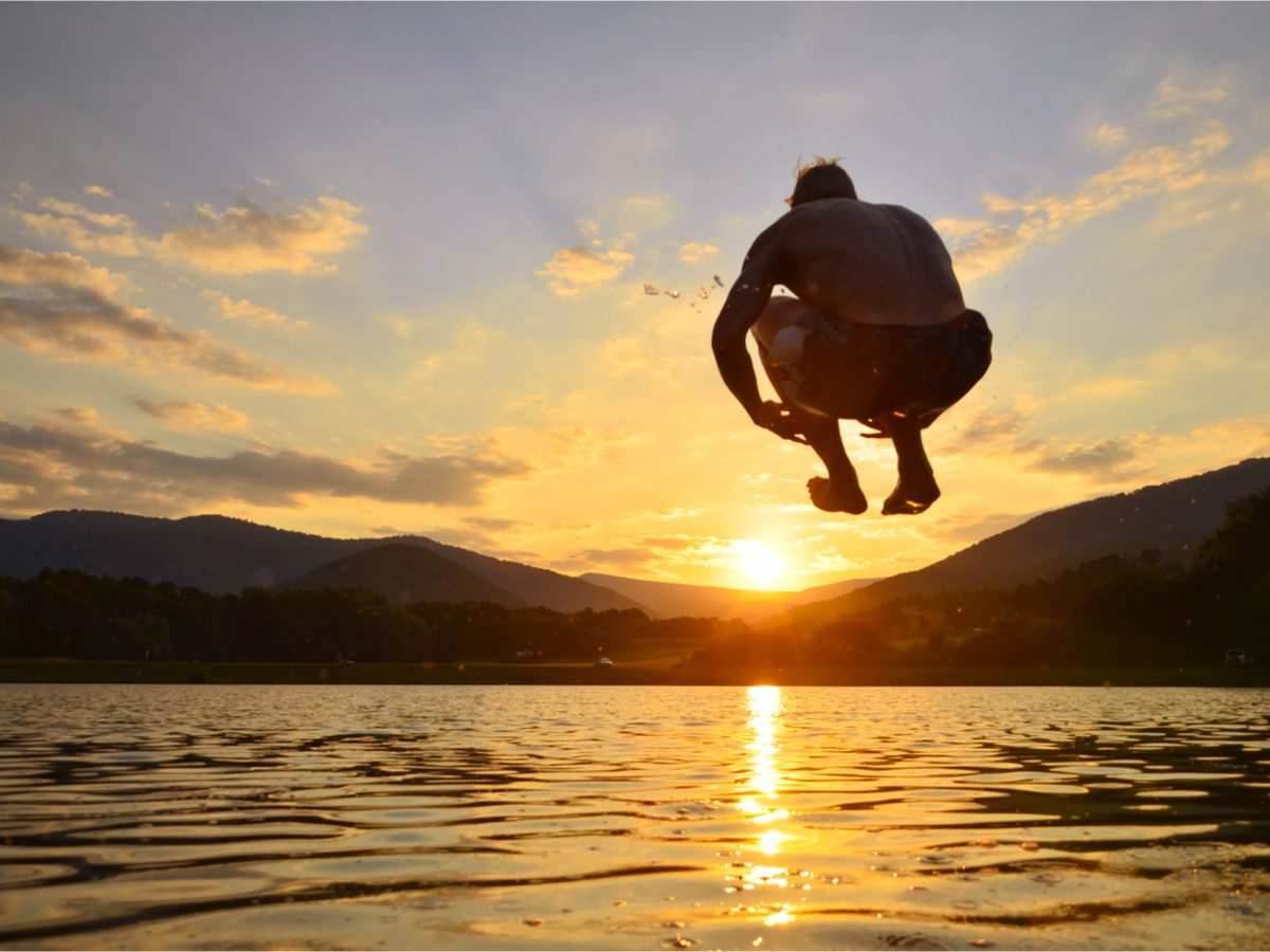 Person jumping into lake