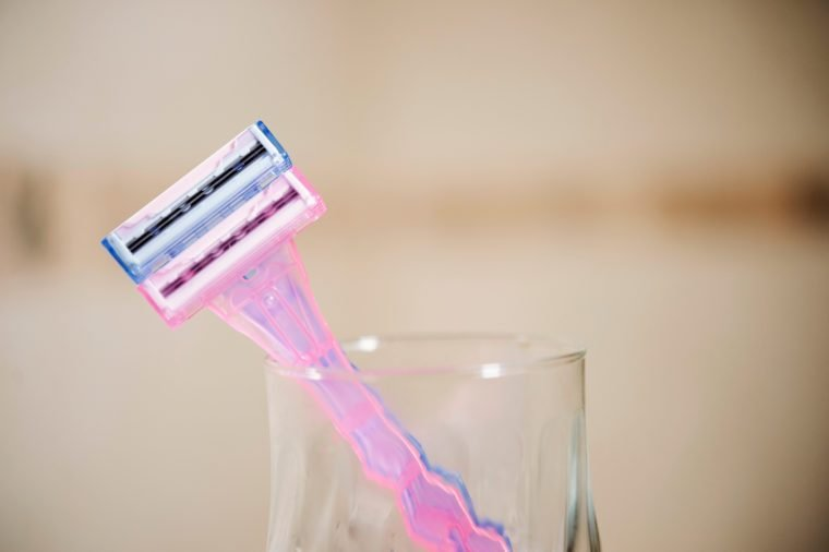 Two plastic blue and pink razors in transparent glass cup in the bathroom