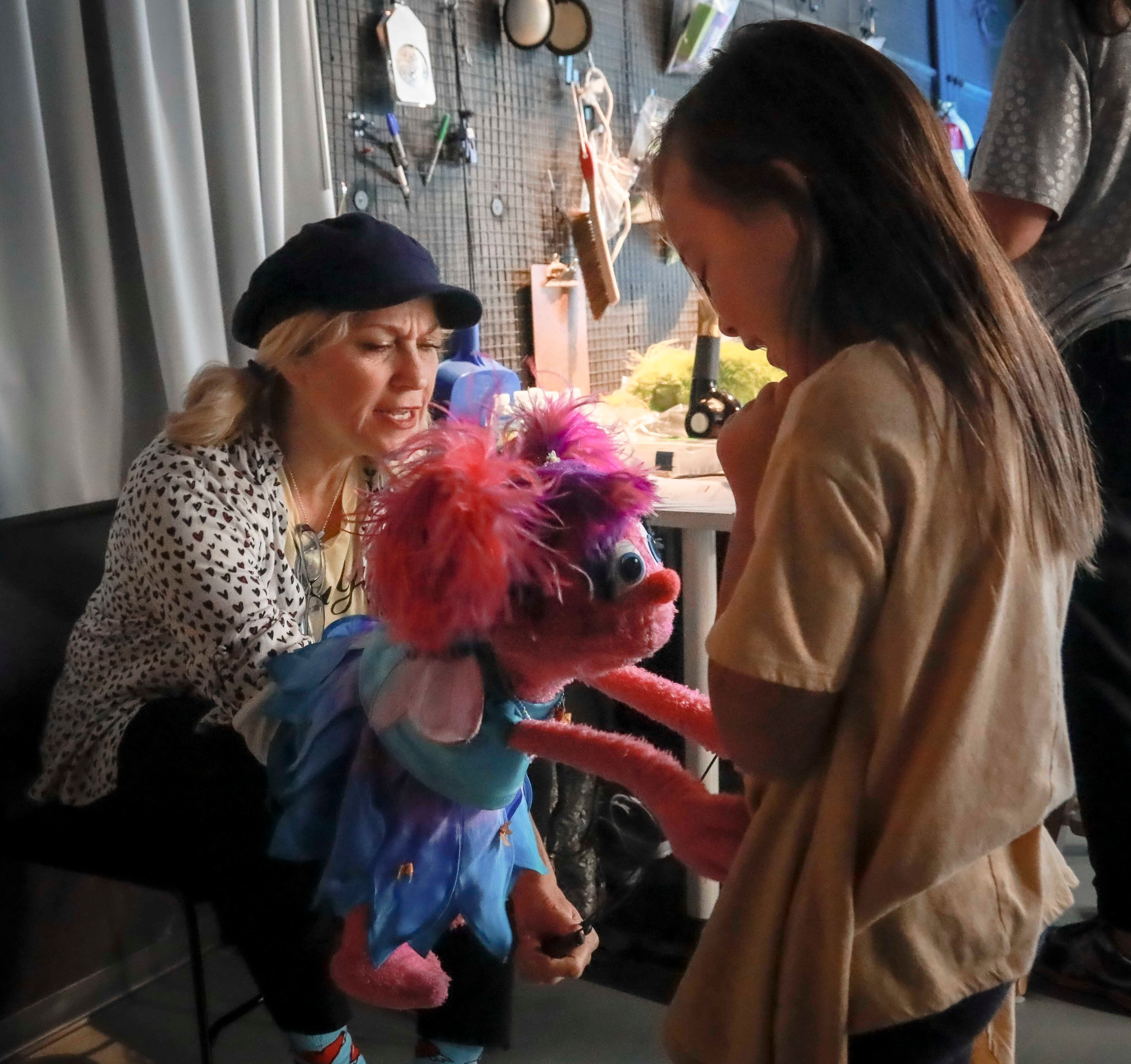 """Mandatory Credit: Photo by Bebeto Matthews/AP/Shutterstock (10465504c) Puppeteer Leslie Carrara-Rudolph, left, performs her muppet """"Abby Cadabby"""" for Kya Woodbury, 6, right, from Irvine, Calif., during a production break for the new Sesame Street Workshop show about parental addiction, """"Sesame Street In Communities,"""", in New York. Kya's older sister Salia is featured in the new program, where she experiences of their parents struggle with addiction and recovery Sesame Street in Communities, New York, USA - 06 Aug 2019"""