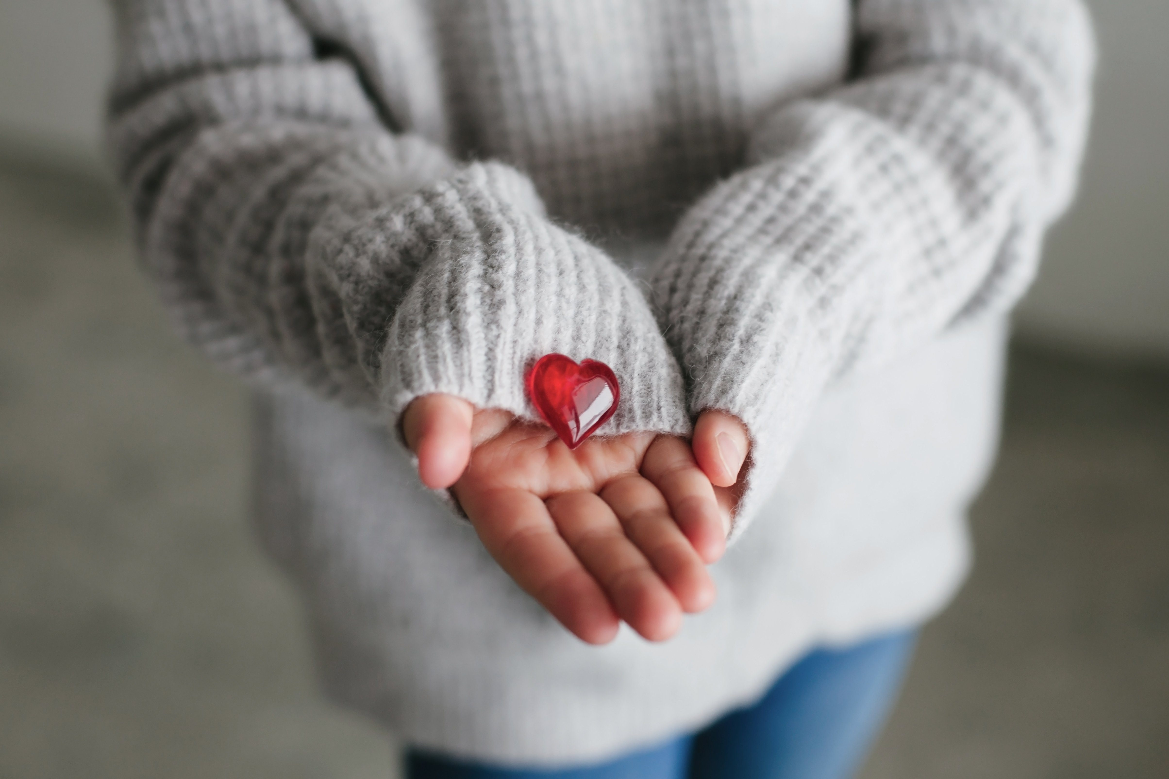 Close up of womans cupped hands showing glass red heart. People, relationship and love concept