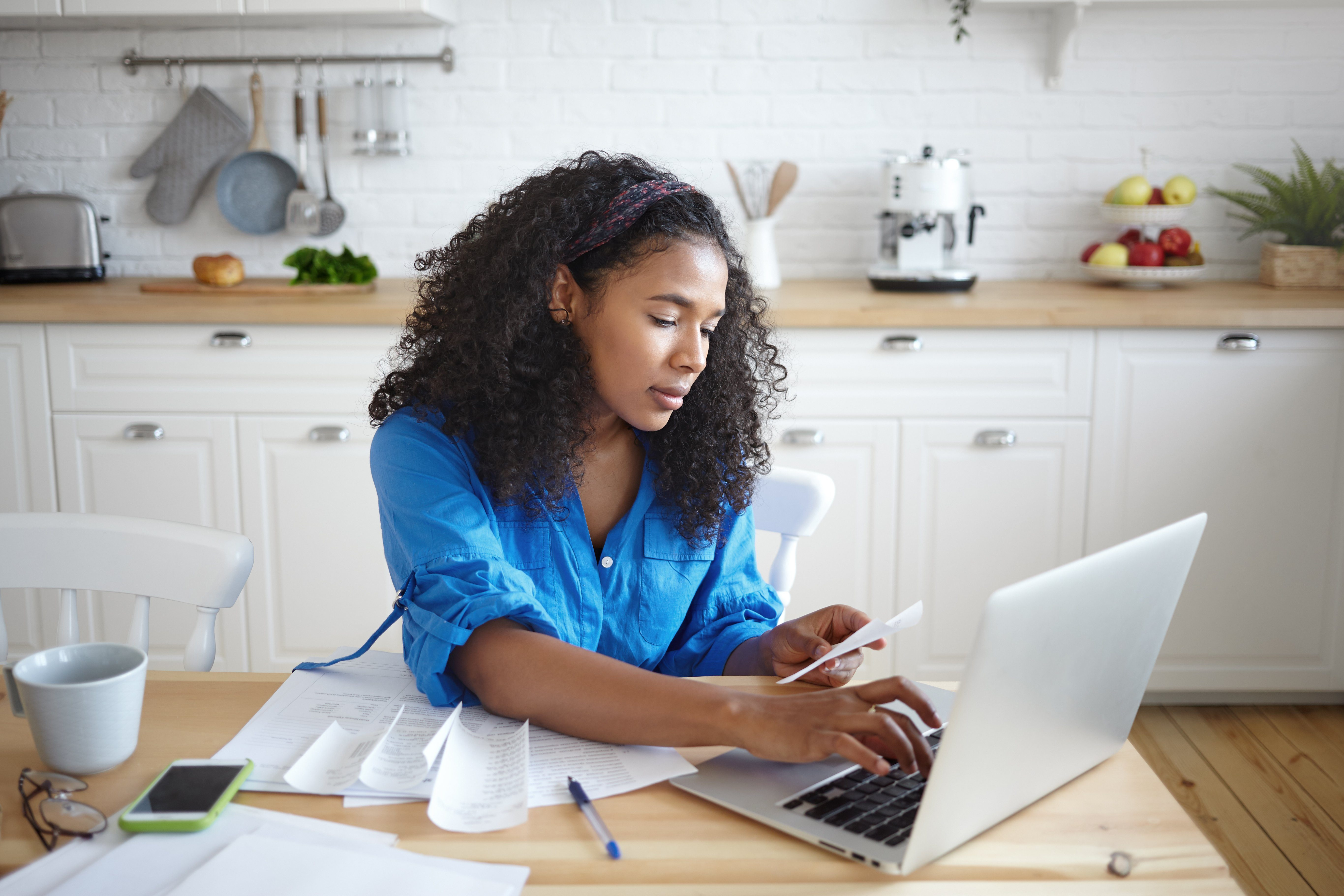 Candid shot of seriousn concentrated young African female using modern technology while paying for gas and electricity online, hoding receipt and typing on laptop. People, finances and home budget