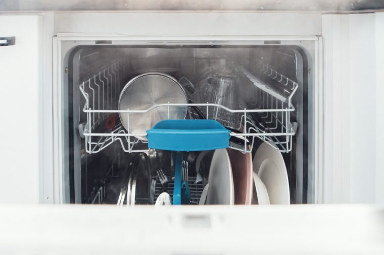 dishwasher for washing dishes, dishwashing machine open for dishware with lots of dishes for dish washing basket cutlery