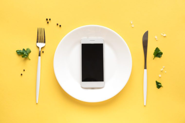 Smartphone on white plate with fork and knife. Food delivery concept on yellow background, top view, copy space.