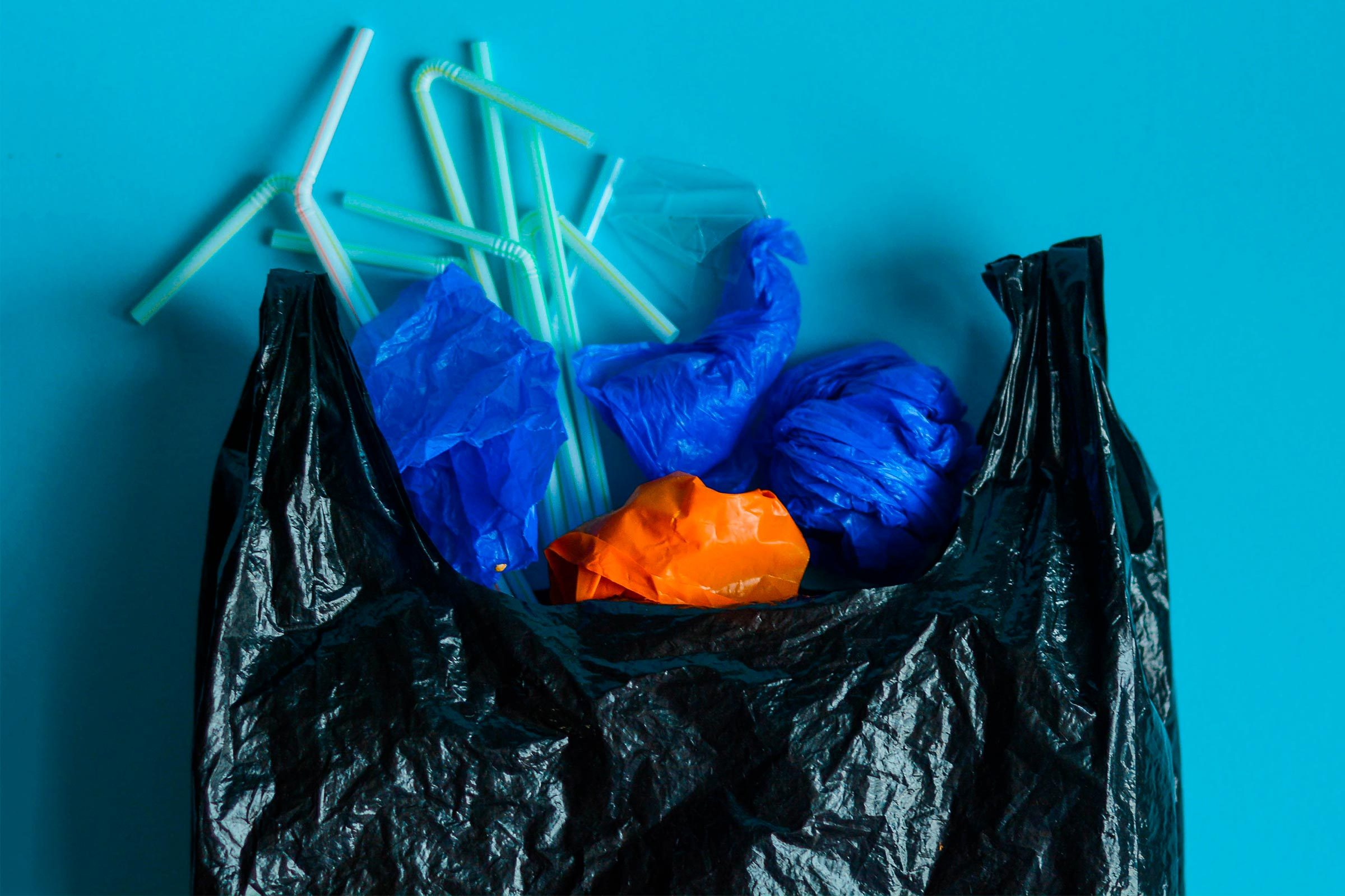 Black plastic bag with variety elements of plastic in it, against a blue background. Representation of plastic pollution