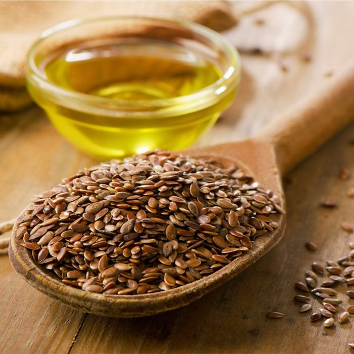 Brown flax seeds on a spoon and flaxseed oil