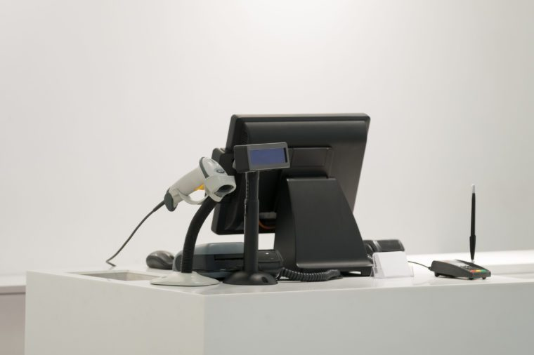 Cash desk with computer screen and barcode scanner on white table and wall in small store