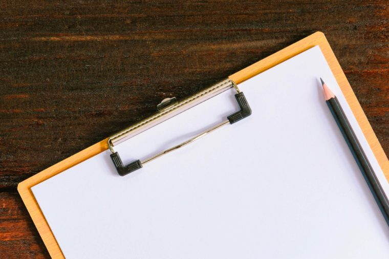 clipboard and pencil on wooden desk